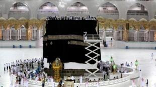 عمال سعوديون يضعون الكسوة الجديدة على الكعبة والمصنوعة من الحرير الأسود والمطرزة بآيات قرآنية، في 29 تموز/يوليو 2020 في مدينة مكة المكرمة بالمملكة العربية السعودية