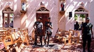 Sri Lankan soldiers keep watch in badly damaged St. Sebastian's Church in the city of Negombo on April 21, 2019, following a series of bomb blasts that killed more than 200, including many foreigners