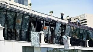 Two men inspect damage from the roof of a restaurant at the Kingsbury Hotel in Colombo on April 22, 2019, a day after it was hit during a series of bomb blasts targeting churches and luxury hotels in Sri Lanka