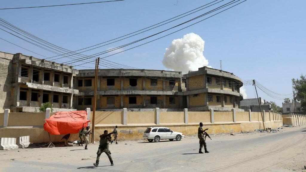 Los oficiales de seguridad somalíes toman posiciones después de una segunda explosión cerca de la residencia del presidente en Mogadiscio, Somalia, el 22 de diciembre de 2018.
