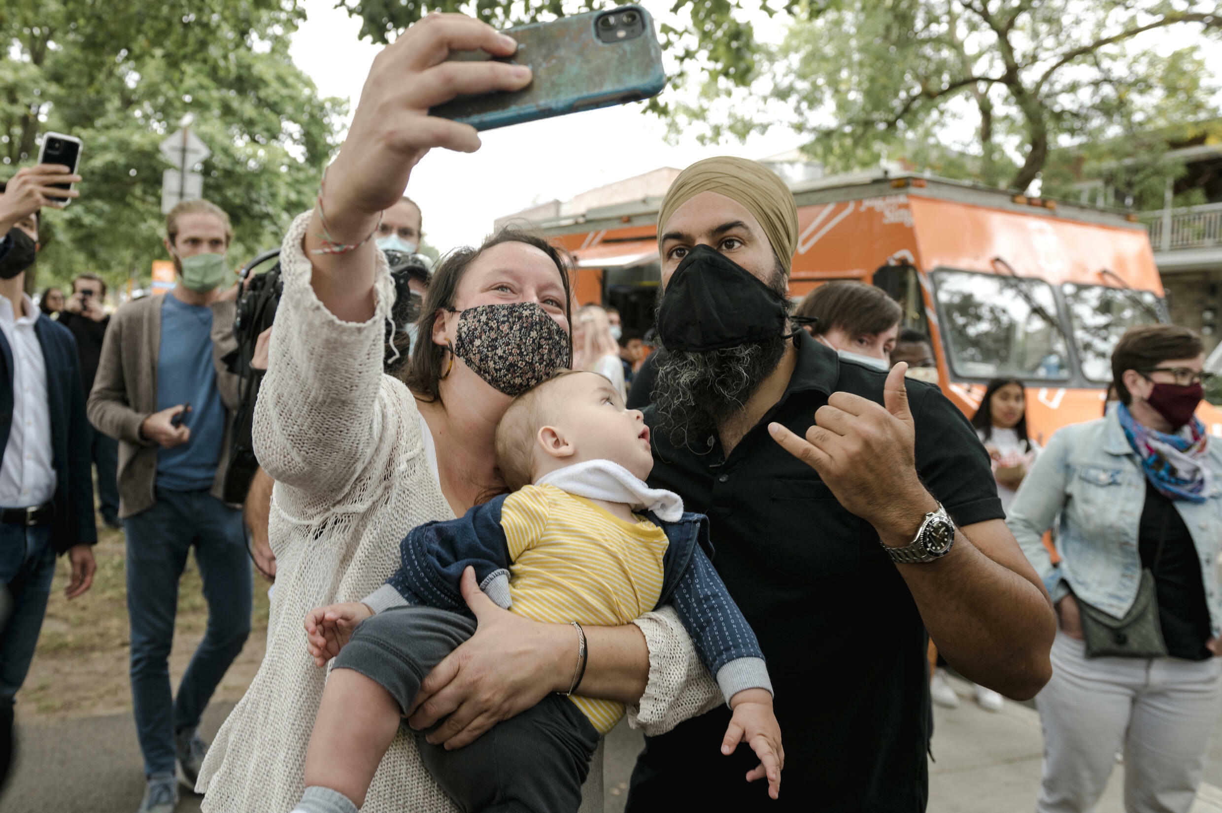 A baby looks at NDP leader Jagmeet Singh as he takes a selfie with a constituant in Montreal after he served his own twist on poutine, Quebec's signature delicacy to voters ahead of the September 20 election