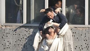 عريس صيني يمسك بزوجته وهي ضابطة محلية تبلغ من العمر 22 عاما ترتدي ثوب زفافها وتحاول الانتحار بالقفز من الطابق السابع في مدينة تشانغتشون بمقاطعة جيلين، 17 مايو/أيار 2011.