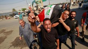 Un doliente manifiesta su indiganción mientras otros llevan el ataúd de un manifestante muerto en las protestas antigubernamentales, durante un funeral en Najaf.