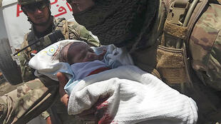 A member of the Afghan security forces carries a baby from a maternity hospital in Kabul that was attacked by gunmen on Tuesday