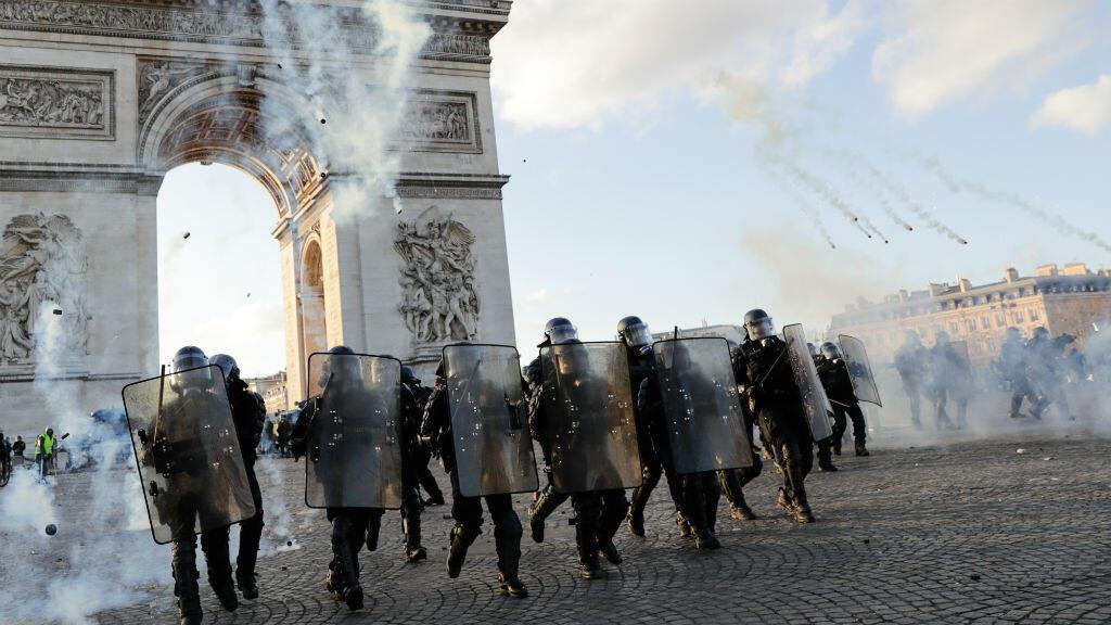 Agentes de la policía antidisturbios se cargan con gas lacrimógeno en el Arco de Triunfo en la Place de l'Etoile en París, el 16 de marzo de 2019.