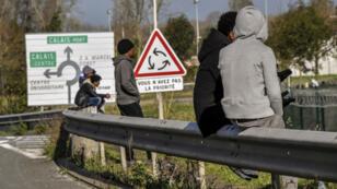 Des migrants assis sur une barrière le long de la route menant au port de Calais, le 2 novembre 2017.