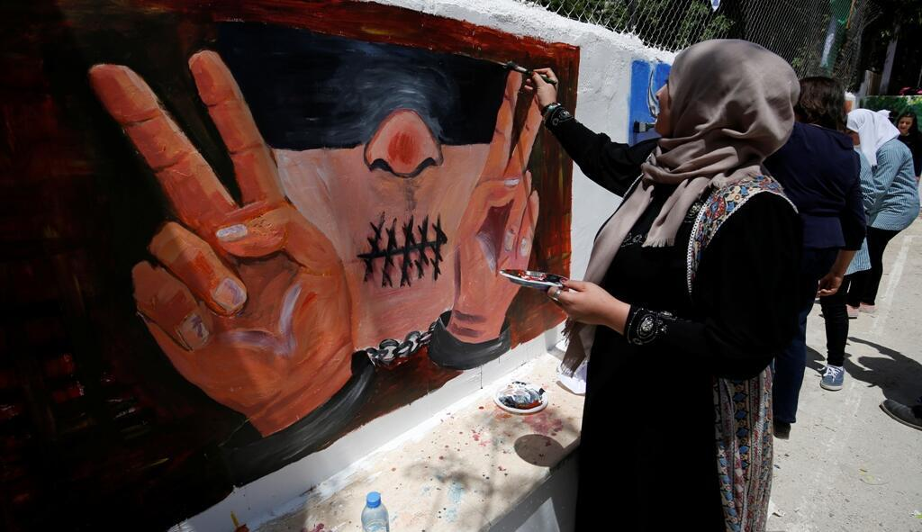 Des femmes palestniennes peignent des motifs sur des murs à l'occasion de la journée des prisonniers palestiniens à Ramallah, le 17 avril 2016.