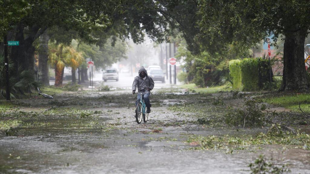 Un hombre conduce su bicicleta por una calle de Charleston que ha sido azotada por los vientos de Dorian.