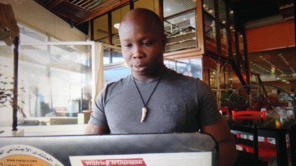 """Le blogueur Daouda """"Sa Majesté"""" Coulibaly depuis son """"bureau"""" du centre commercial de Deux-Plateaux, à Abidjan."""