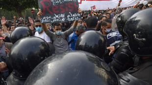 Members of the Tunisian police confront protesters demonstrating against the government and police repression in the capital Tunis on February 6, 2021.