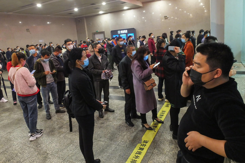 La gente hace fila para comprar billetes de tren en la estación ferroviaria de Yichang Este, el 25 de marzo de 2020 en la ciudad china de Yichang, en la provincia de Hubei.