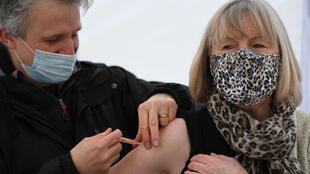 (FILES) In this file photo taken on February 08, 2021 Health workers administer Covid-19 vaccines at a drive through vaccination centre at Batchwood Hall in St Albans, north of London on February 8, 2021.
