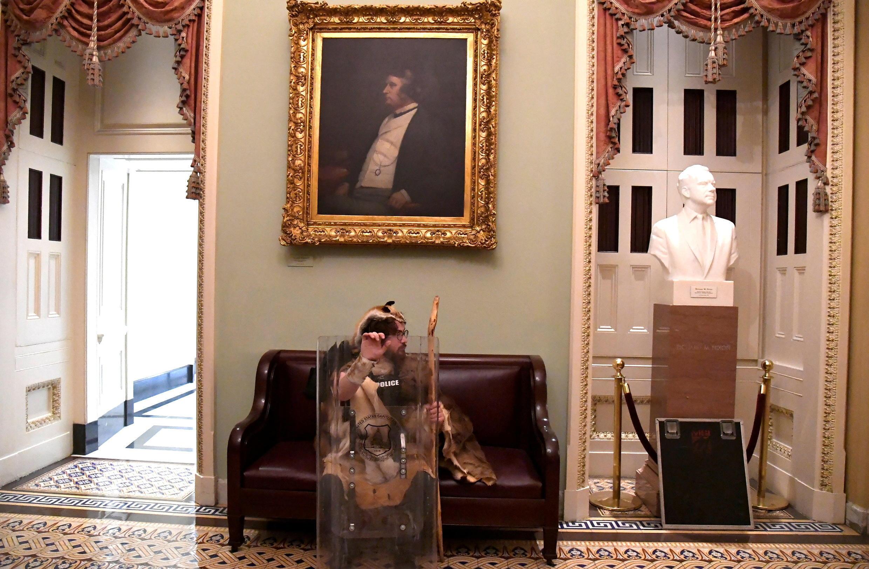 Un manifestant s'assoie pour se reposer sous un portrait du deuxième étage du Capitole.