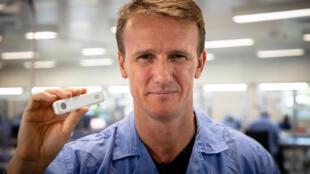 El CEO de Ellume Sean Parsons enseña un kit de su prueba doméstica de covid-19
