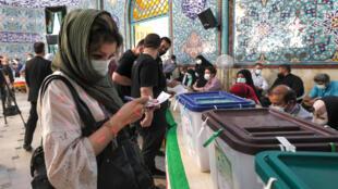 امرأة ايرانية امام صناديق اقتراع في احد المراكز في طهران في 18 حزيران/يونيو 2021