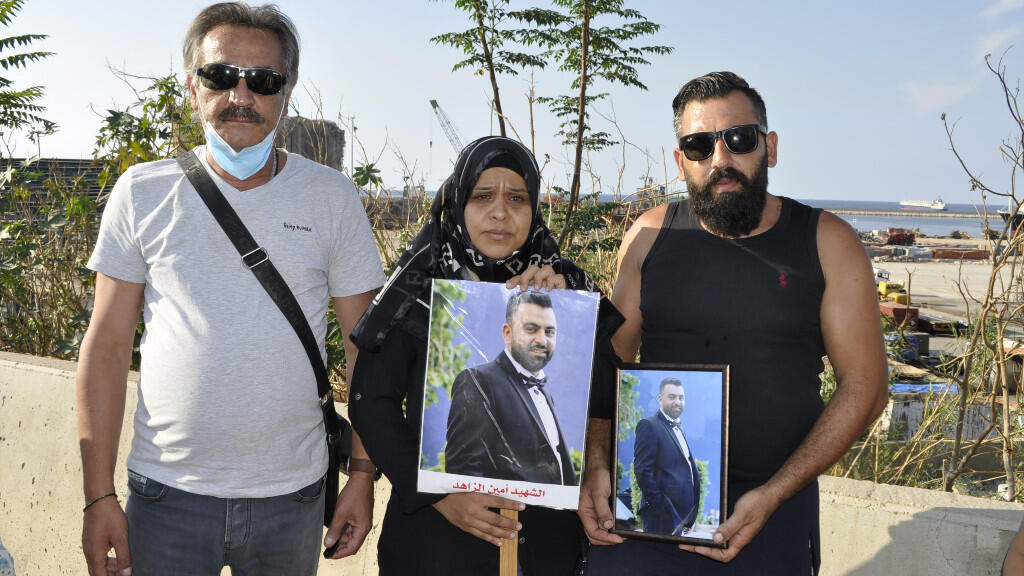 Rima Zahed, pictured alongside two members of her family, holds a portrait of her brother Amine, who died on August 4 in the port of Beirut.