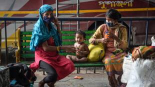 Unos trabajadores migrantes y sus familias que viajan del estado indio de Kerala al de Assam, varados en una estación de autobús en Siliguri, por el confinamiento, el 16 de julio de 2020