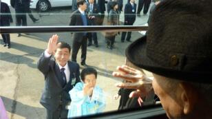 En esta foto tomada el 22 de febrero de 2014, el surcoreano Kim Se-Rin (Der.) se despide desde un autobús de su hermana norcoreana Kim Young-Sook (cent.) y su sobrino Kim Ki-Bok (izq.) al irse de una reunión familiar en la zona turística del Monte Kumgang, Corea del Norte.