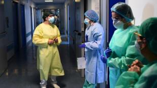La italiana Cristina Preti (L), presidenta del personal de limpieza del hospital de Cremona, habla con el personal médico en el área de terapia intensiva Covid-19 del hospital, el 22 de abril de 2020.