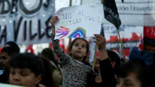 Una niña sostiene un cartel contra la violencia policial enl una manifestación en San Miguel del Monte, en Argentina, el viernes 24 de mayo