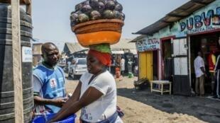 امرأة تطهر يديها أمام موظف صحي في 15 تموز/يوليو في مدينة غوما، شرق جمهورية الكونغو الديمقراطية حيث شخصت الحالة الأولى لوباء إيبولا