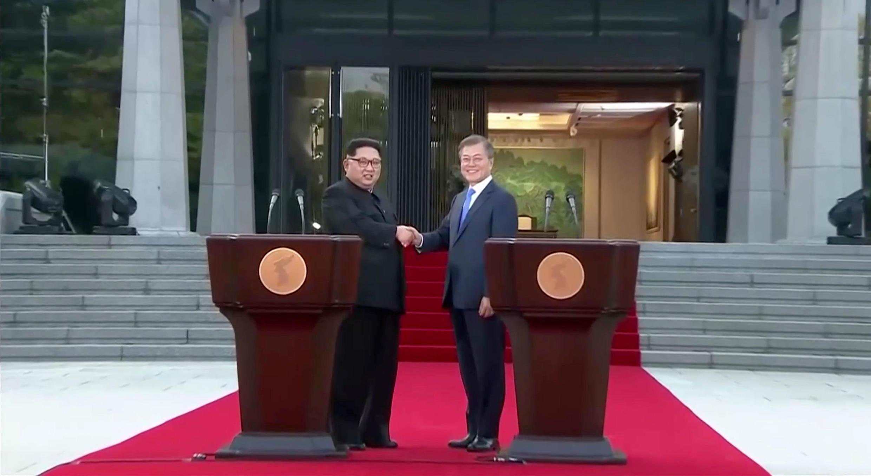 El líder de Corea del Norte Kim Jong-un y el presidente surcoreano Moon Jae-in se dan la mano en una imagen de la transmisión televisada. 27/4/18