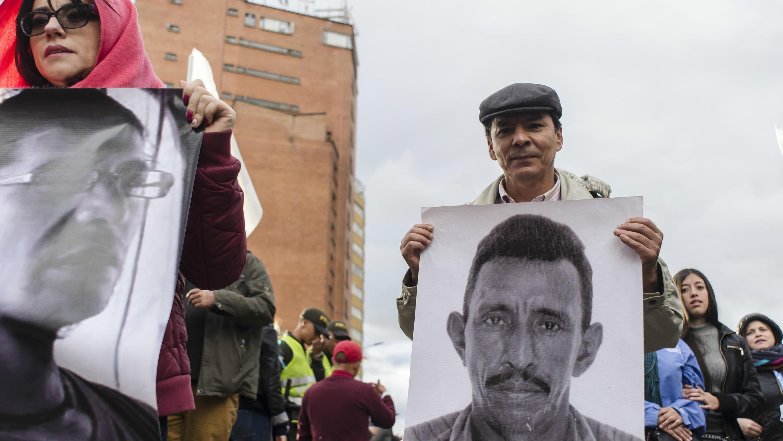 Manifestantes sosteniendo retratos de líderes sociales asesinados durante una marcha en Bogotá el 26 de julio de 2019.