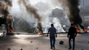 متظاهرون يسيرون بالقرب من متاريس أثناء احتجاجات منددة بالظروف الاقتصادية