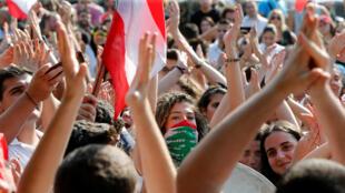 Estudiantes hacen gestos y llevan banderas nacionales en una manifestación cerca de la central eléctrica de Zouk, durante las protestas contra el gobierno en Zouk, al norte de Beirut, Líbano, el 7 de noviembre de 2019.