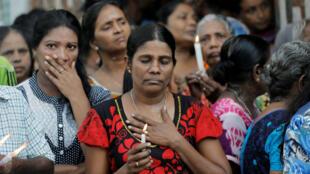 Varias personas guardan silencio como homenaje a las víctimas, dos días después del atentado con bombas ocurrido en varias iglesias y hoteles de lujo el domingo de Pascua, en Colombo, Sri Lanka, el 23 de abril de 2019.