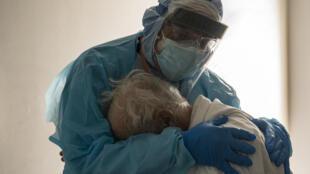 Le Dr Joseph Varon réconforte un patient âgé atteint du Covid-19 le 26 novembre 2020 à l'hôpital United Memorial de Houston, au Texas