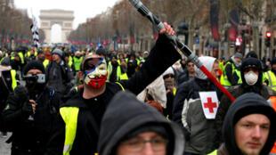 Un manifestante que usa un chaleco amarillo, una máscara anónima y un láser de luz Jedi de Star Wars participa en una demostración del movimiento 'chaleco amarillo' en París, Francia, el 15 de diciembre de 2018.
