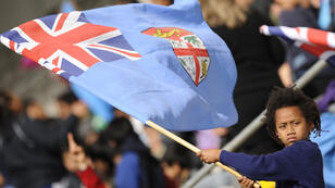 A child waves the flag of Fiji at the 2011 Rugby World Cup in New Zealand