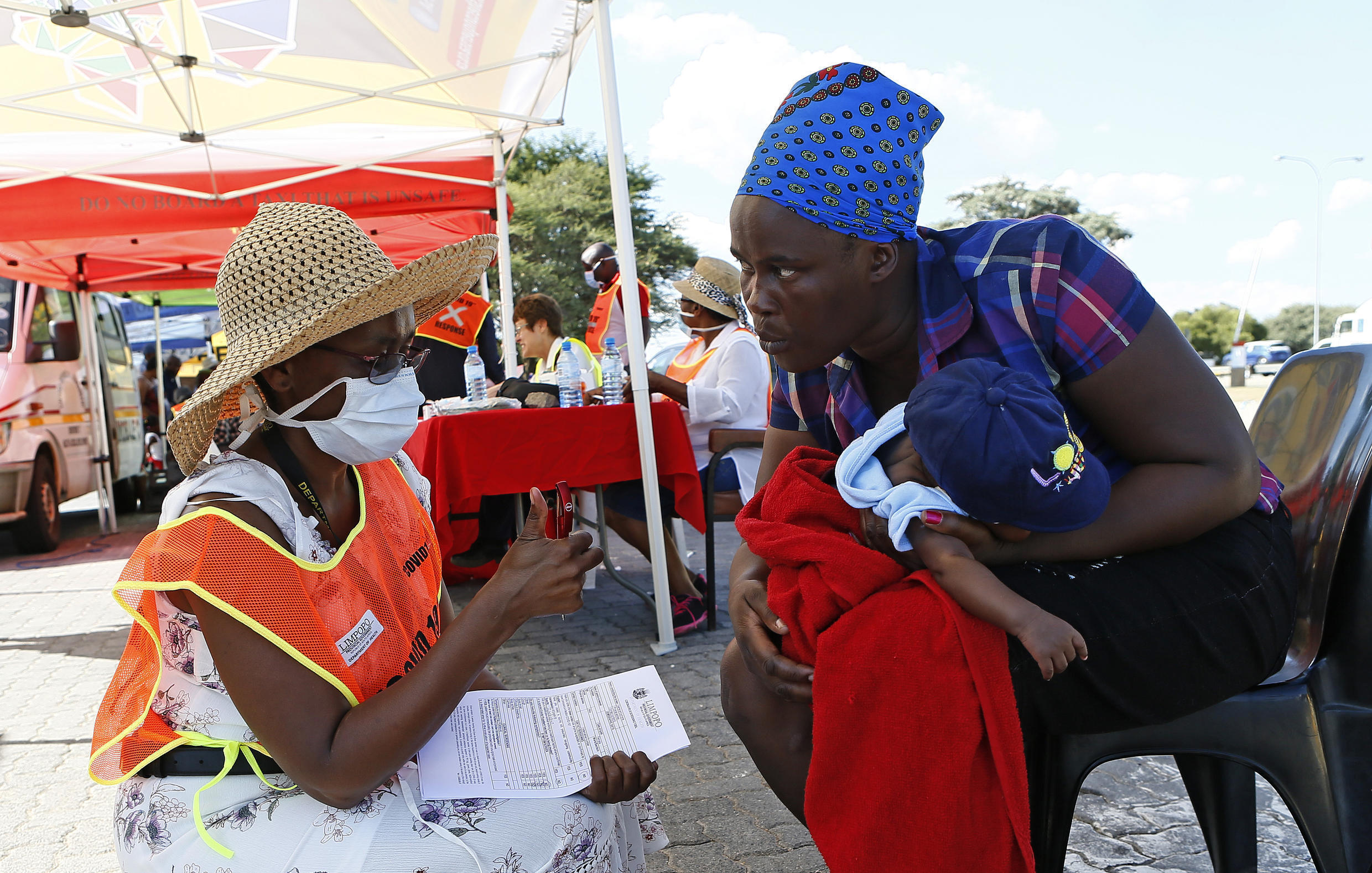 A Limpopo provincial health official gives a thumbs up after conducting a screening test on a traveller carrying a baby while making her way from Gauteng to Limpopo ahead of the nationwide lockdown in South Africa on March 25, 2020.