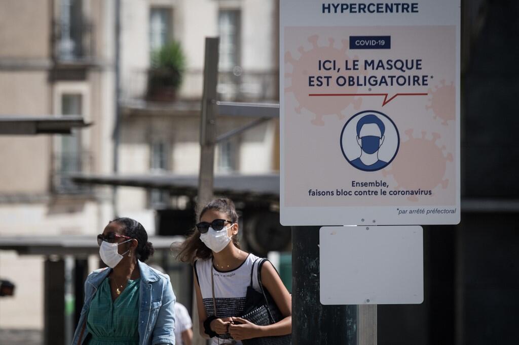 """Transeúntes usan máscaras protectoras mientras pasean por una calle junto a un letrero que dice """"aquí la máscara es obligatoria"""", en Nantes, oeste de Francia, el 21 de agosto de 2020."""