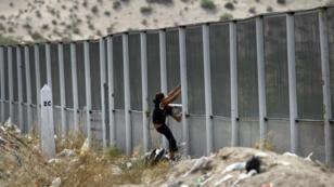 Une jeune Mexicaine escalade un pan d'un ancien de mur de séparation à la frontière entre le Mexique et les États-Unis.