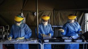 Personal sanitario sudafricano rellena documentos antes de realizar unas pruebas de detección del coronavirus a otros colegas de trabajo, el 15 de abril de 2020 en una tienda de campaña instalada en el hospital Charlotte Maxeke de Johannesburgo
