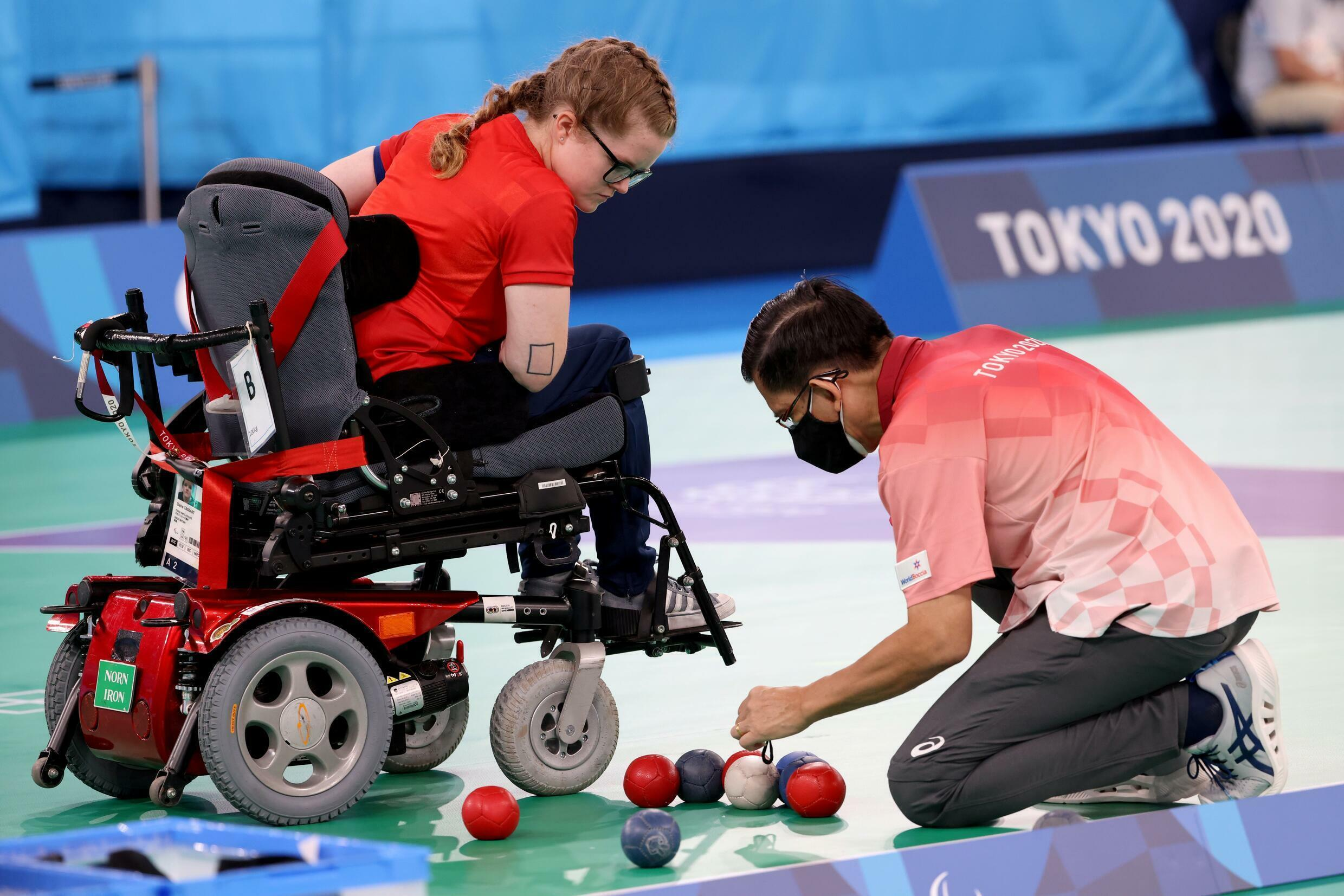 Briton Claire Taggart checks as the referee measures the distance between balls during her match against Argentinian Luis Cristaldo in the individual class BC2 of boccia