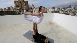 Lebanese yoga instructor Rabih el-Medawar, 29, practises Acroyoga with his Ukranian wife, fellow yoga instructor and professional choreographer, Alona Aleksandrova, 24, on the roof of their apartment building in Beirut, Lebanon on April 27, 2020.