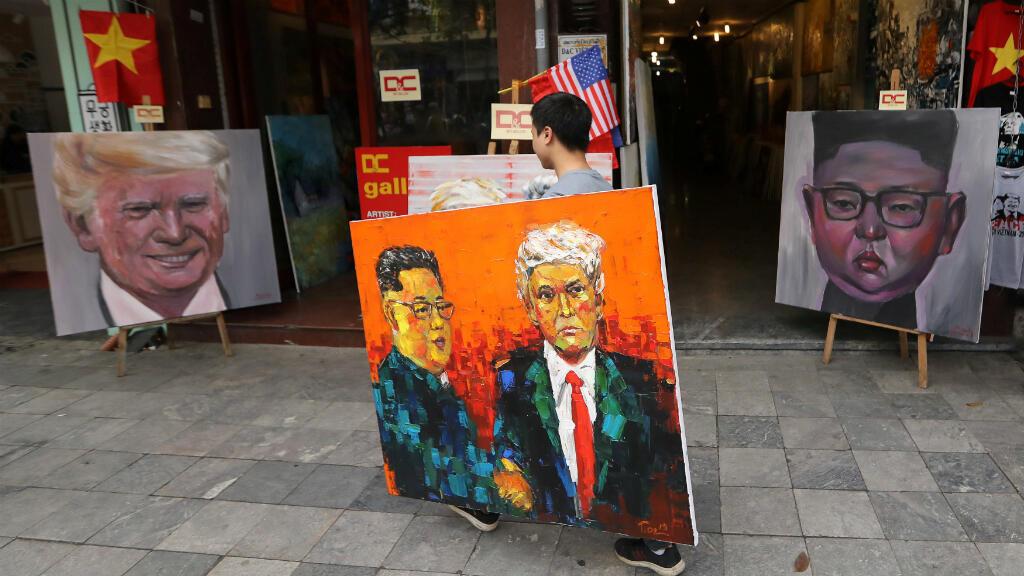 Un hombre sostiene una pintura del líder norcoreano Kim Jong-un y el presidente de Estados Unidos Donald Trump, pasa por delante de las pinturas de Kim y Trump, en Hanói, Vietnam, el 27 de febrero de 2019.