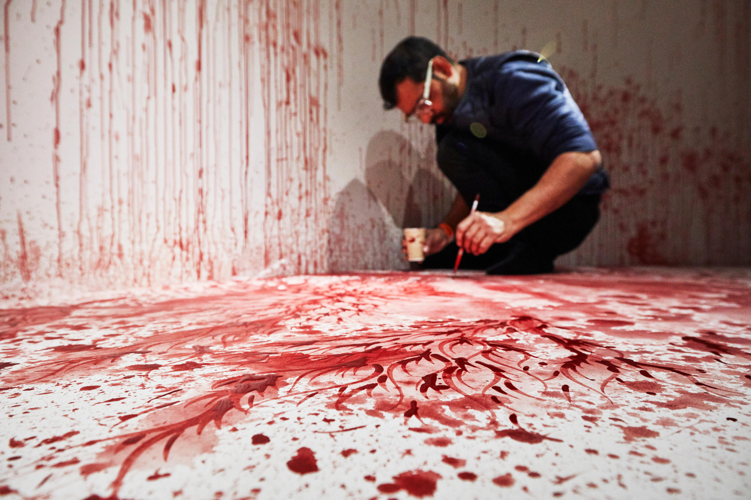 """Pakistani artist Imran Qureshi at work on """"This too will end,if you go on a step or two,"""" an installation at the Louboutin retrospective."""
