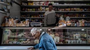 El vendedor de comestibles ambulante Claude Mottet sonríe a una clienta e el interior de su camión durante una visita a la localidad de Romans-sur-Isere, el 17 de abril de 2020 al este de Francia