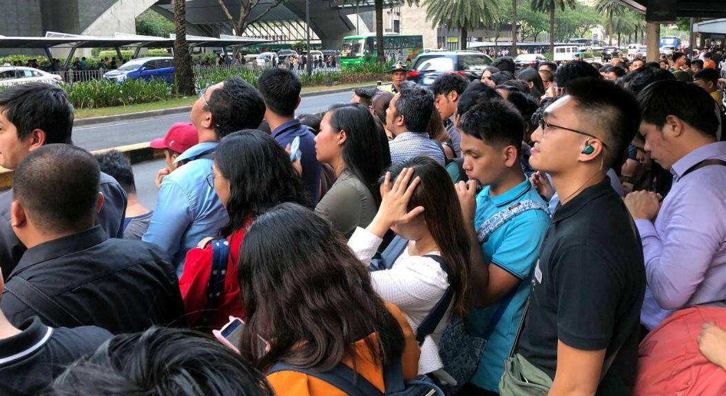 Empleados del distrito comercial de Manila, Filipinas, esperan afuera de los edificios, tras ser evacuados por un terremoto de 6.3 de magnitud en la escala de Richter, el 22 de abril de 2019.
