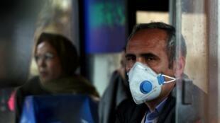 مواطن إيراني يرتدي كمامة واقية من العدوى تحسبا لانتشار فيروس كورونا، طهران. 25 فبراير/شباط 2020.