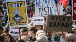 """A demonstrator holds a placard reading """"#Demisi"""" (C) during a protest against the government led by Andrej Babis in Wenceslas Square in Prague, Czech Republic on May 21, 2019"""