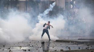 Un manifestante arroja gas lacrimógeno mientras protesta contra el modelo económico estatal de Chile en Santiago, el 23 de octubre de 2019.