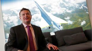 Blake Scholl, co-fondateur de Boom Supersonic pose devant une représentation du Concorde.