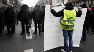 A protestor wearing a yellow vest faces off with CRS riot police during a demonstration in Paris as part of the 36th consecutive day of strike against French government's pensions reform plans in France, January 9, 2020.