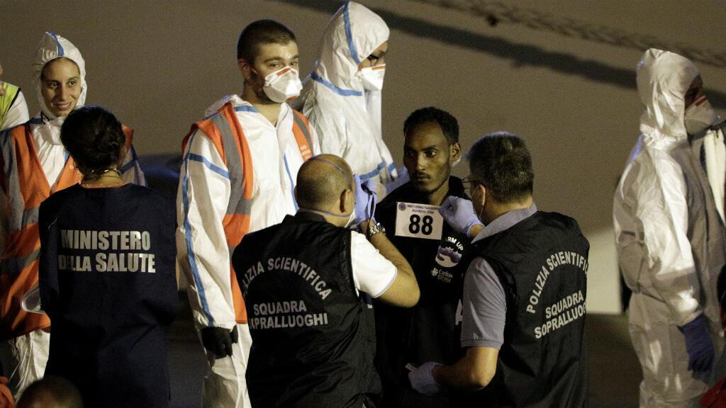 """Un migrante es revisado por miembros de la policía forense después de desembarcar del buque de la guardia costera italiana """"Diciotti"""" en el puerto de Catania, Italia, el 26 de agosto de 2018."""