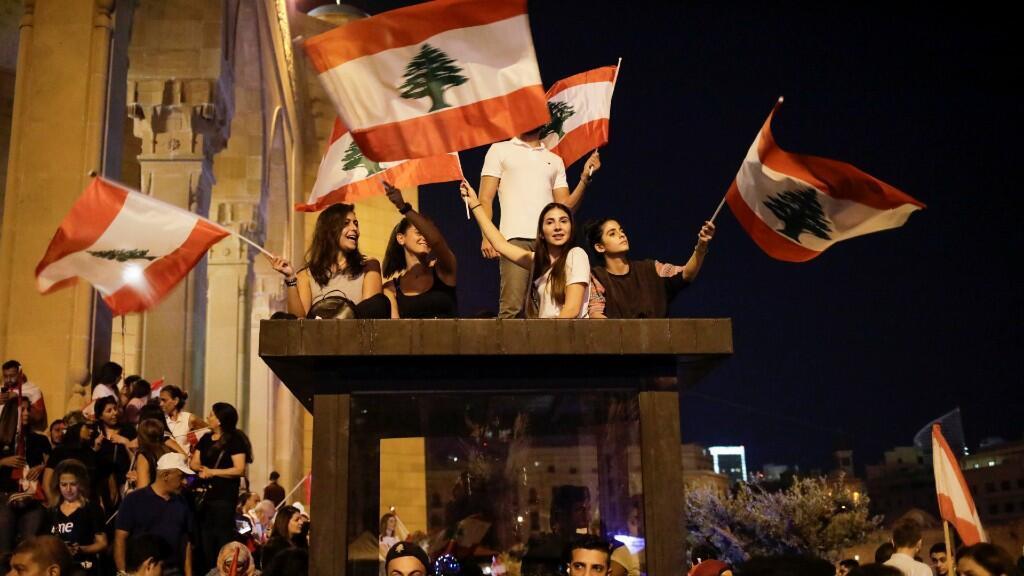 Oficiales de policía hacen guardia mientras los manifestantes ondean banderas libanesas en una manifestación en la Plaza de los Mártires, durante las continuas protestas antigubernamentales en Beirut el 10 de noviembre de 2019.
